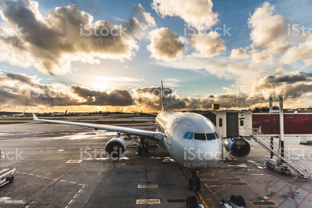 Avião de passageiros no aeroporto de embarque ao pôr do sol - foto de acervo