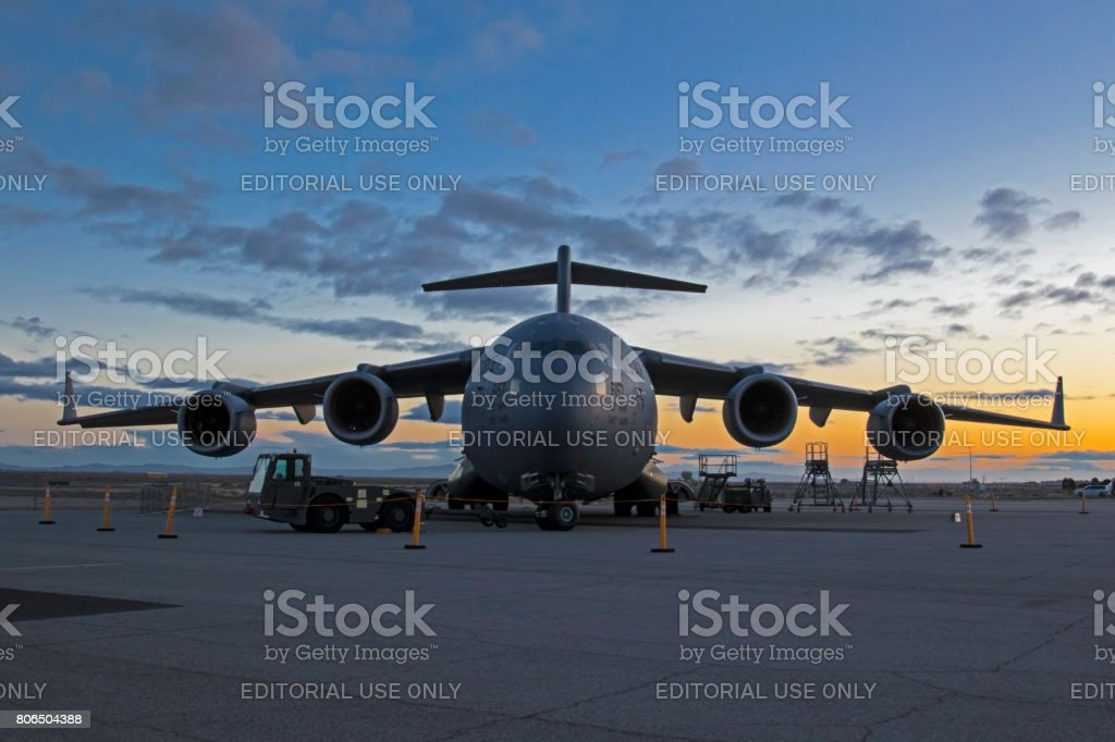 Airplane C-17 Troop Transport military jet aircraft at sunrise stock photo