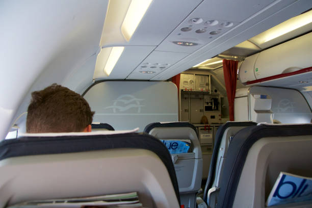 Airplane cabin, business class interior seats, passenger after takeoff stock photo