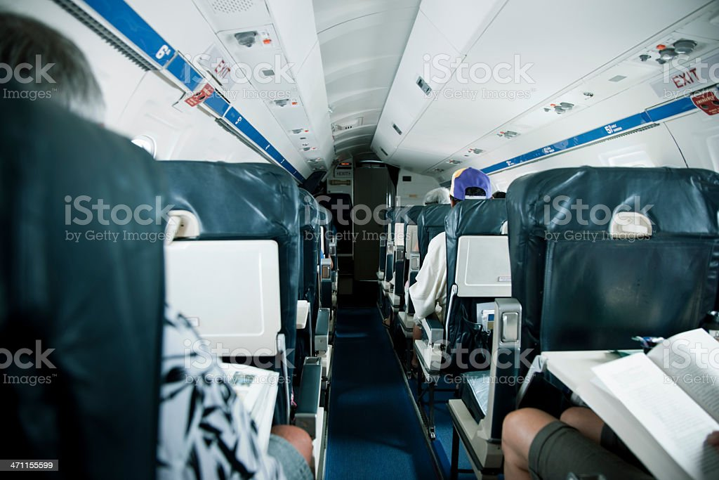 Airplane Cabin with Passengers during Flight stock photo