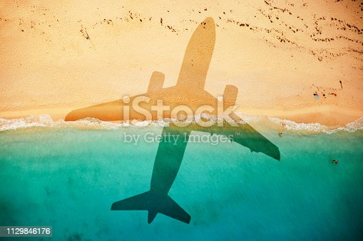 Airplane casts a shadow on the beach. Concept for vacation and holidays.