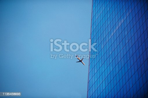 182061540 istock photo Airplane close to a skyscraper building perspective Blue 1135458693