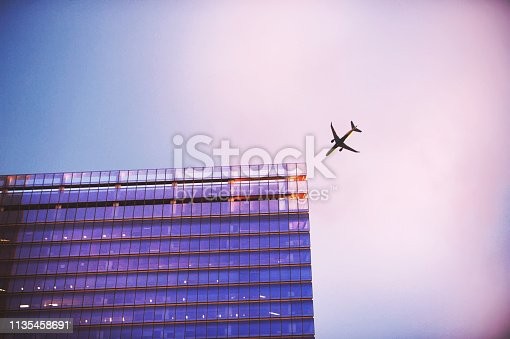 182061540 istock photo Airplane close to a skyscraper building perspective Pink Purple 1135458691