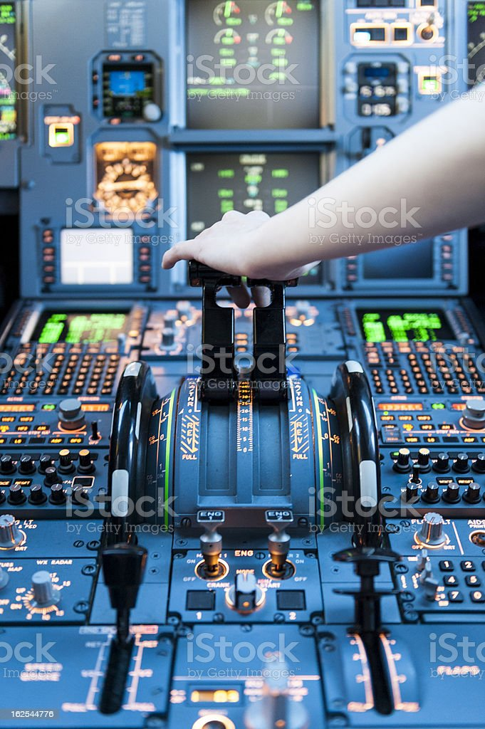 Airplane Cockpit Thrust levers with hand on top. stock photo
