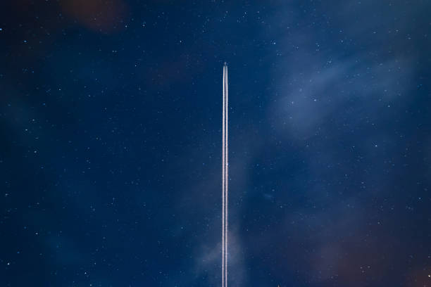 Airplane contrail against clear blue sky stock photo