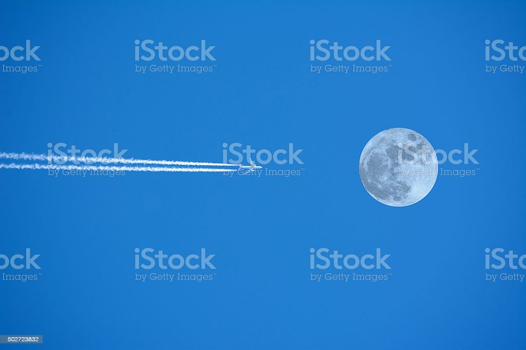 Airplane crossing the moon stock photo