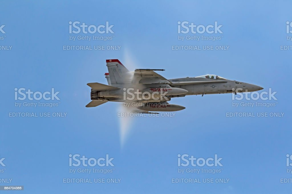 Airplane F-18 Hornet jet fighter approaches the speed of sound displaying a vapor cone stock photo