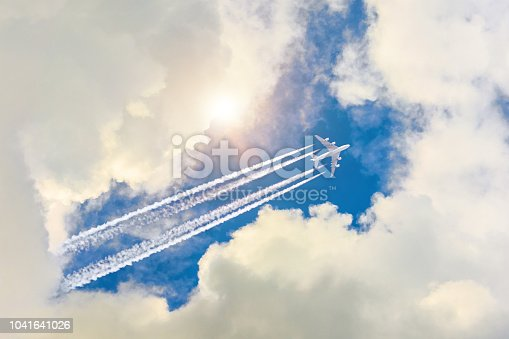 istock Airplane flies high in the sky, a journey through the clouds and a sunny glare. 1041641026