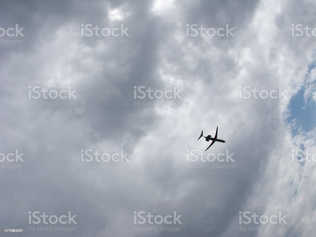 Airplane flies in a cloudy sky royalty-free stock photo