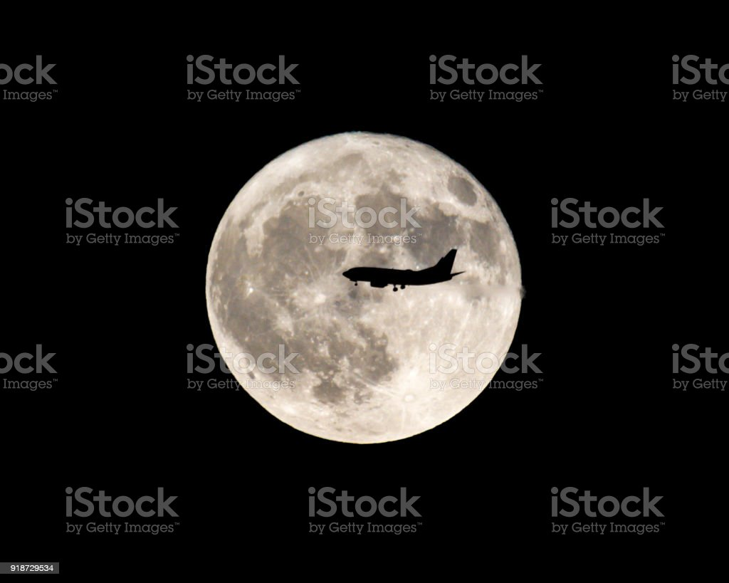 Airplane flies in front of full moon stock photo