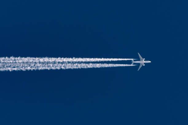 Airplane flies leaving contrail trace on a clear high blue sky. Airplane flies leaving contrail trace on a clear high blue sky supersonic airplane stock pictures, royalty-free photos & images