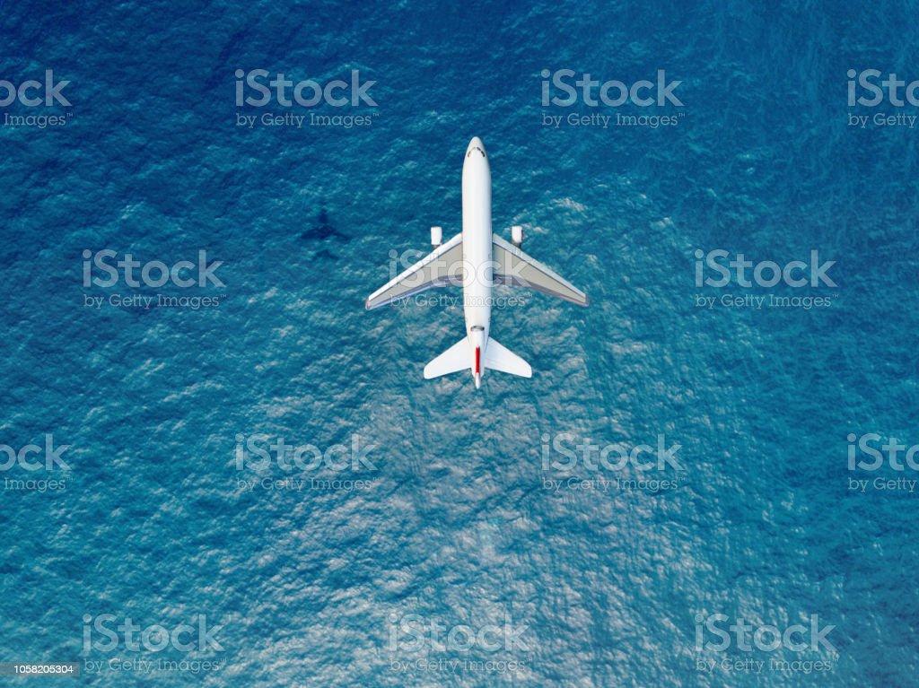 Airplane flies over a sea Airplane flies over a sea Above Stock Photo