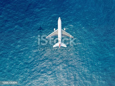 istock Airplane flies over a sea 1058205304