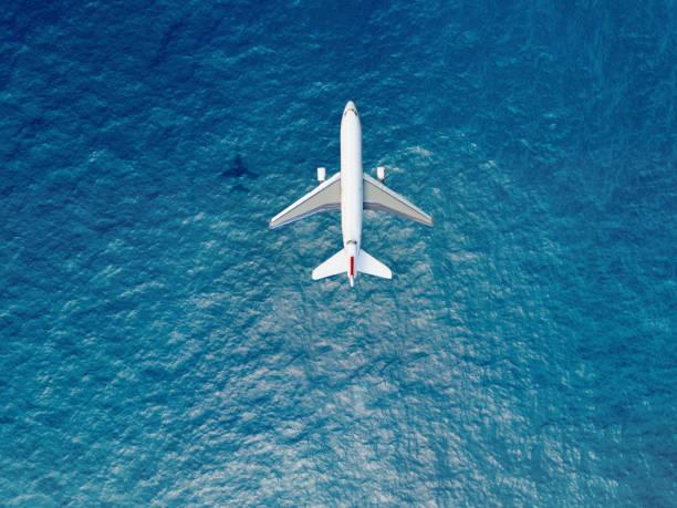 avión vuela sobre un mar - avión fotografías e imágenes de stock