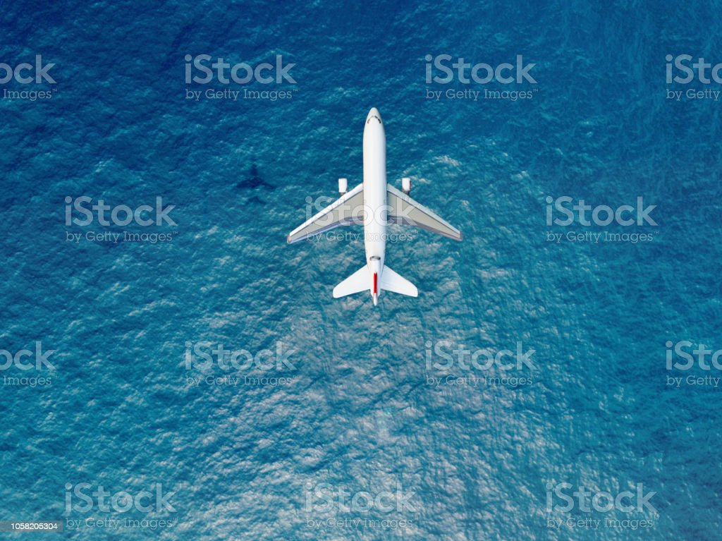 Airplane flies over a sea stock photo