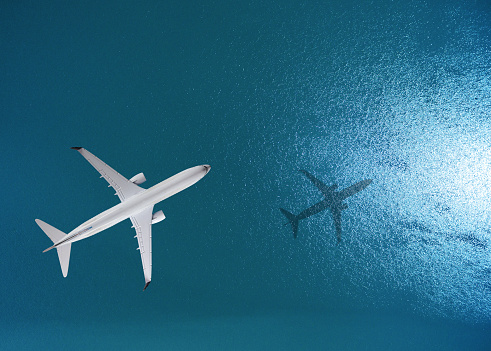 istock Airplane flies over a sea 836102536