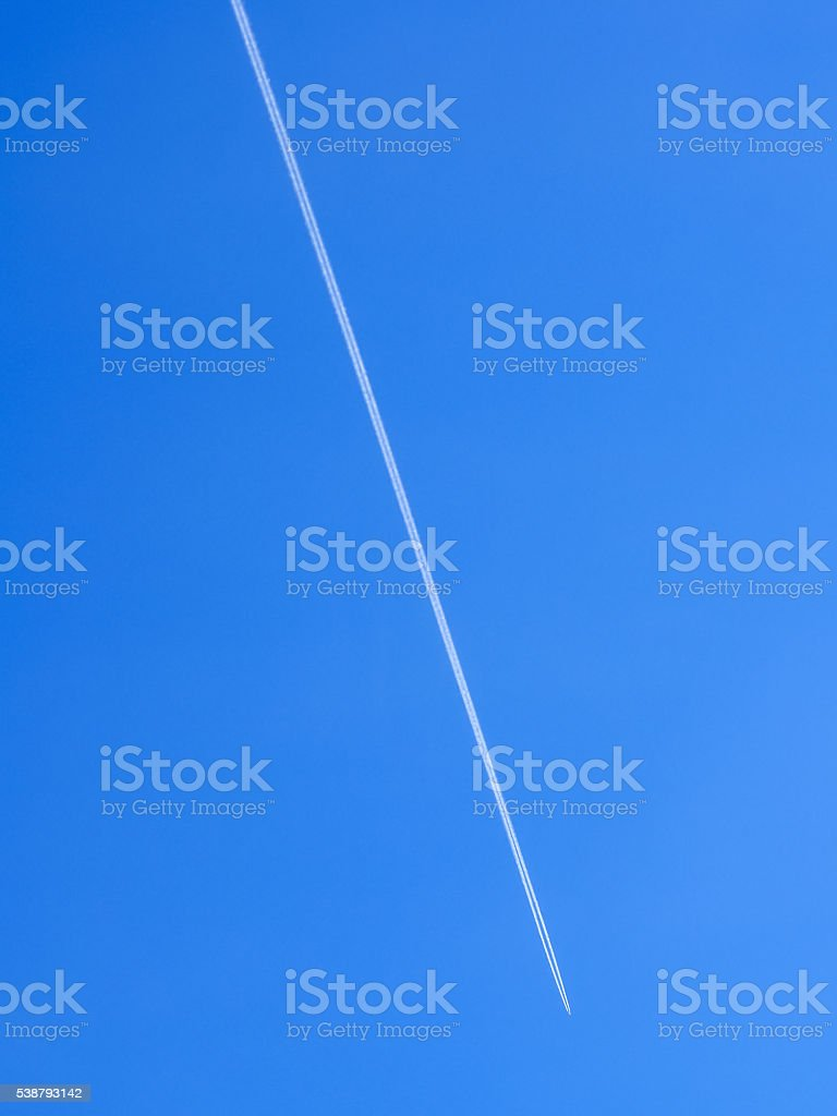 Airplane flight path in the clear blue sky leaving condensation stock photo