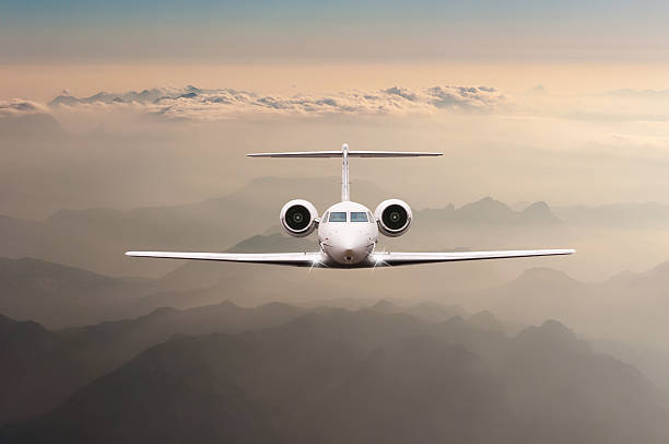 Airplane fly over clouds and Alps mountain on sunset. Front Airplane fly over clouds and Alps mountain on sunset. Front view of a big passenger or cargo aircraft, business jet, airline. Transportation and travel concept. military private stock pictures, royalty-free photos & images