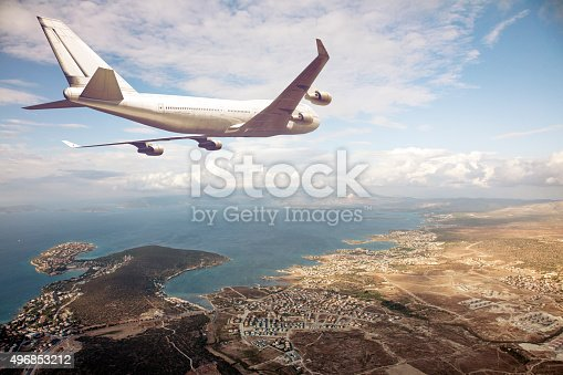 istock airplane flying above a seaside city 496853212