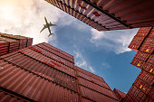 istock Airplane flying above container logistic. Cargo and shipping business. Container ship for import and export logistic. Logistic industry from port to port. Container at harbor for truck transport. 1257175043