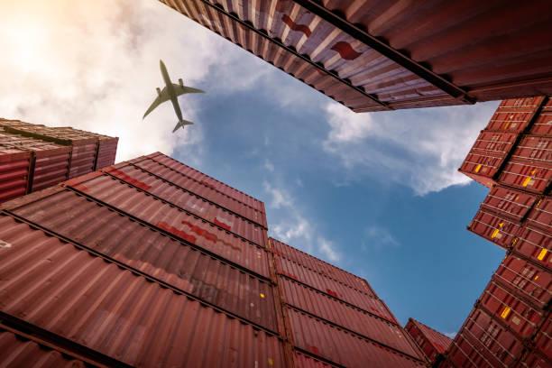 flugzeug fliegt über containerlogistik. fracht- und schifffahrtsgeschäft. containerschiff für import- und exportlogistik. logistikindustrie von hafen zu hafen. container am hafen für den lkw-transport. - fracht stock-fotos und bilder