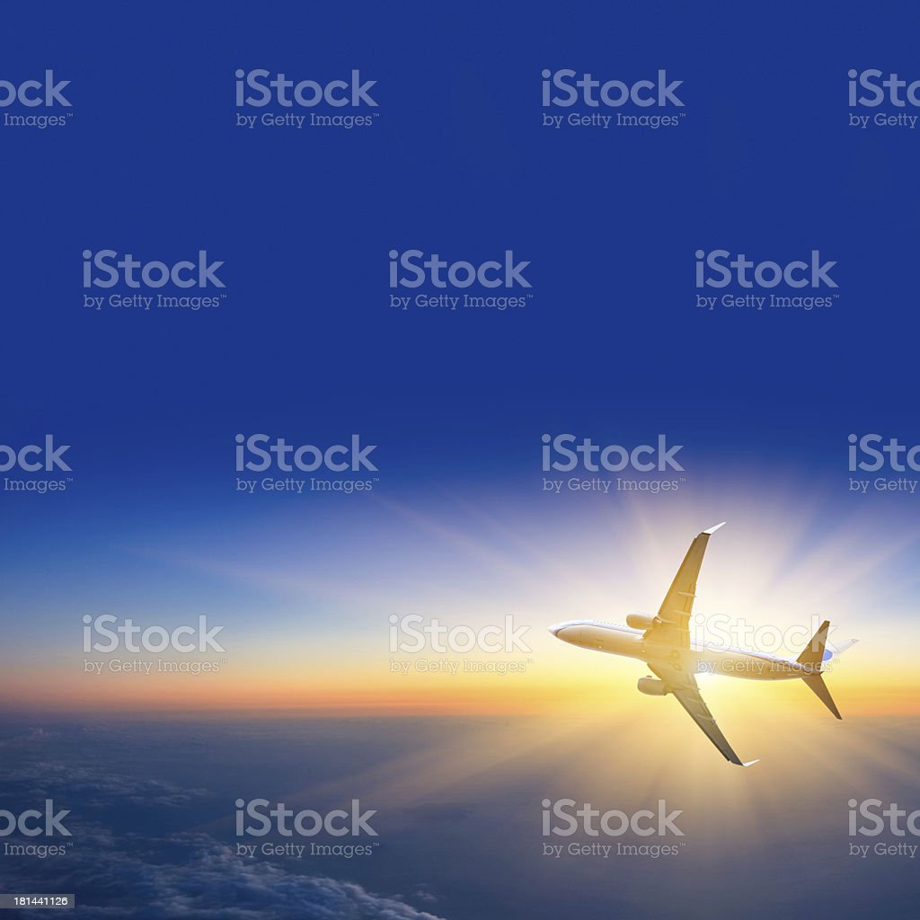 Airplane flying above earth in to sun stock photo