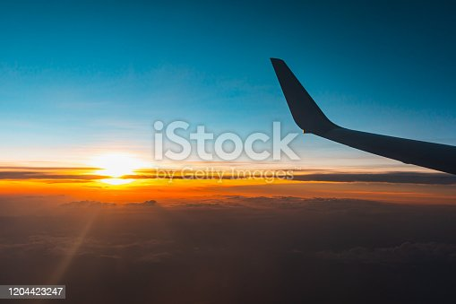 902818356 istock photo Airplane flying above the clouds at sunset. 1204423247