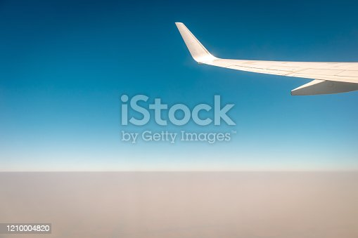 902818356 istock photo Airplane flying above the clouds at sunset 1210004820