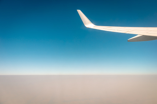 621114928 istock photo Airplane flying above the clouds at sunset 1210004820