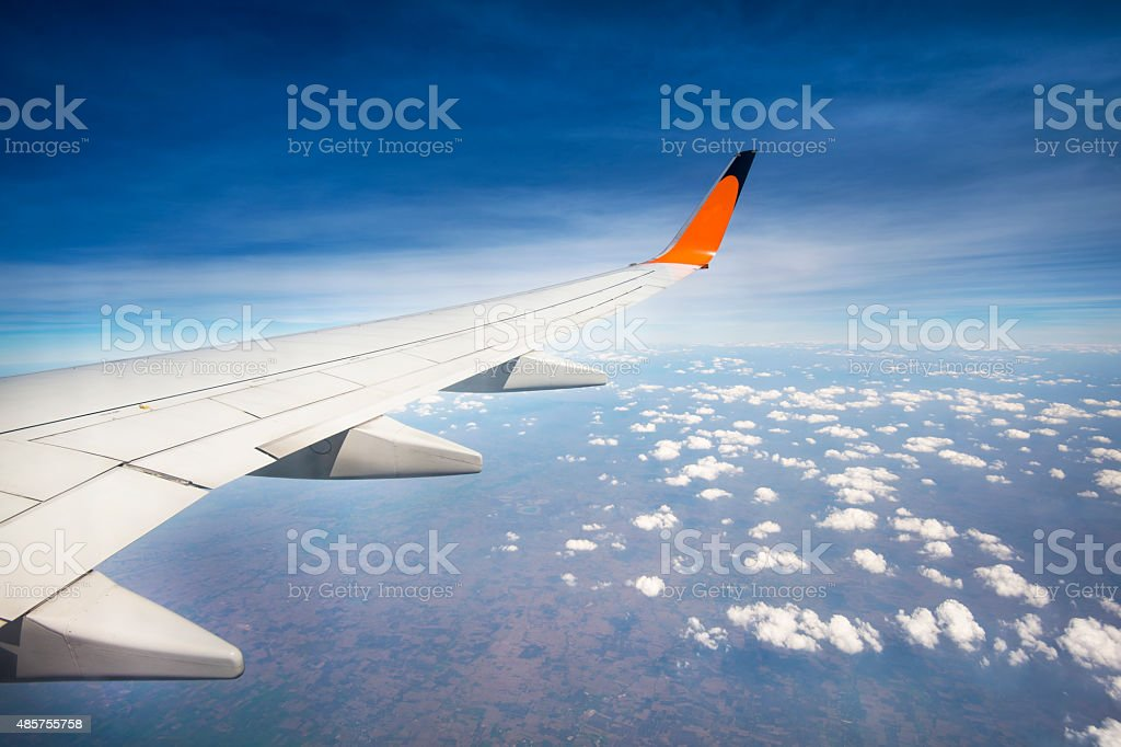 airplane flying above the clouds in the sky stock photo
