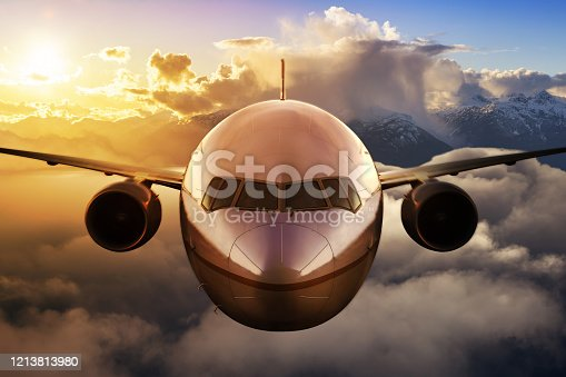 Airplane flying above the clouds during colorful sunset or sunrise. Concept of Travel, transportation, aviation, journey, adventure