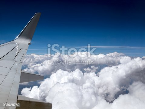 istock Airplane flying above the white Cumulus clouds in the blue sky 925925780