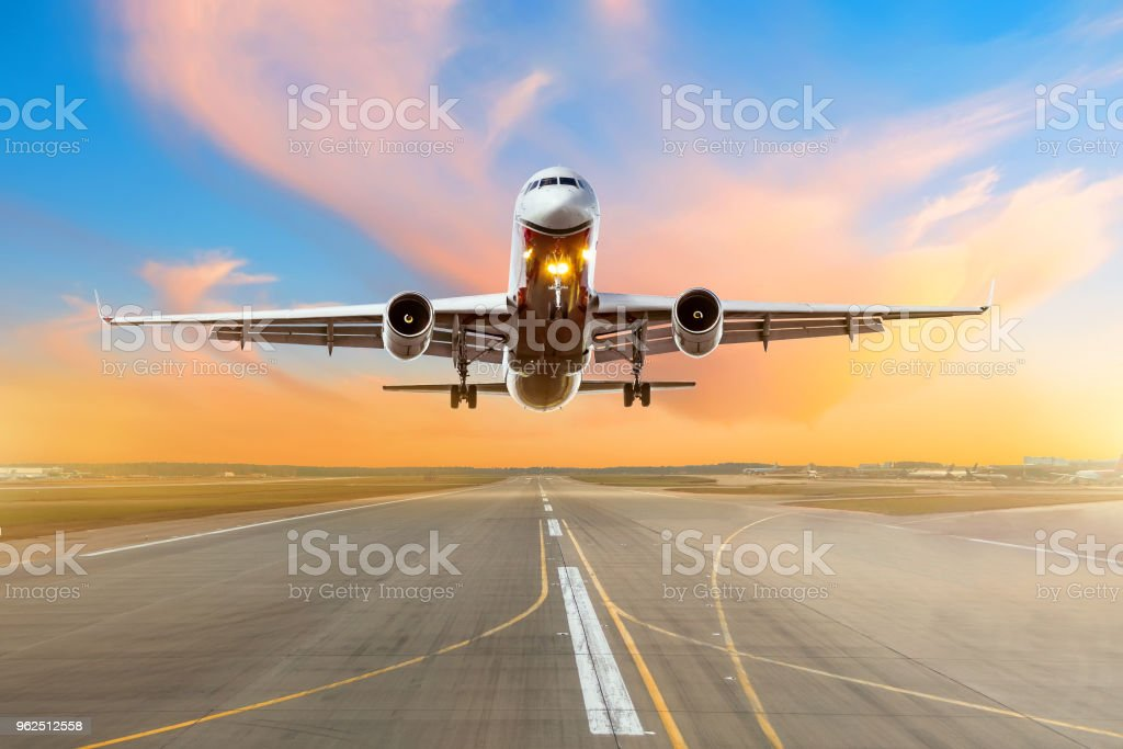 Airplane flying arrival landing on a runway in the evening during a bright red sunset. stock photo