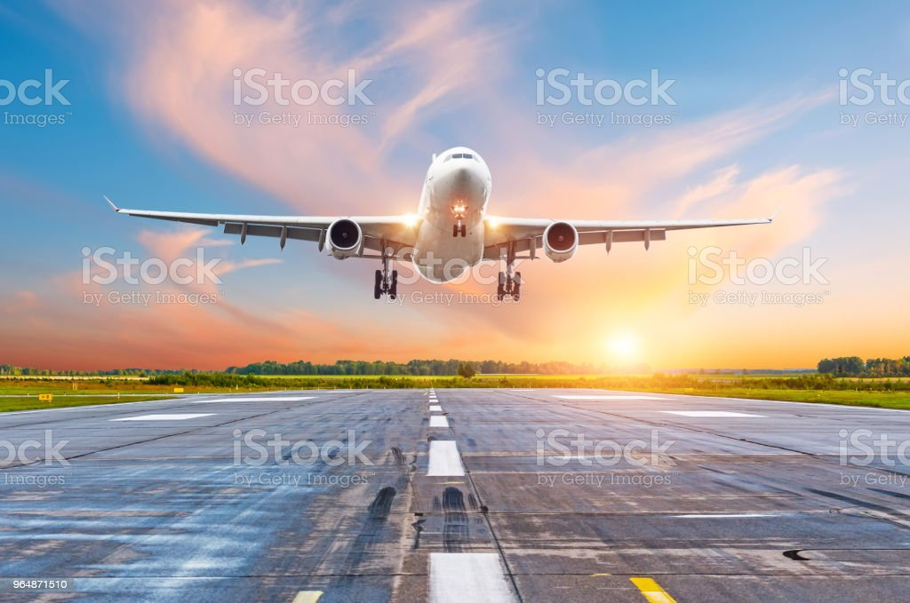 Airplane flying arrival landing on a runway in the evening during a bright red sunset sunshine. royalty-free stock photo