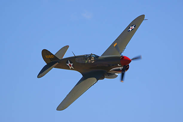 P-40 WWII airplane flying at air show Chino, California,USA- May 2,2015. Vintage WWII P-40 Warhawk airplane flying at 2015 Planes of Fame Air Show in Chino, California. The 2015 Planes of Fame Air Show features 3 days of vintage and modern military aircraft performing and many static aircraft displays open to the public. bomber plane stock pictures, royalty-free photos & images