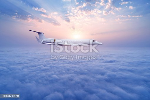 Airplane flying in the high altitude sky at sunrise.