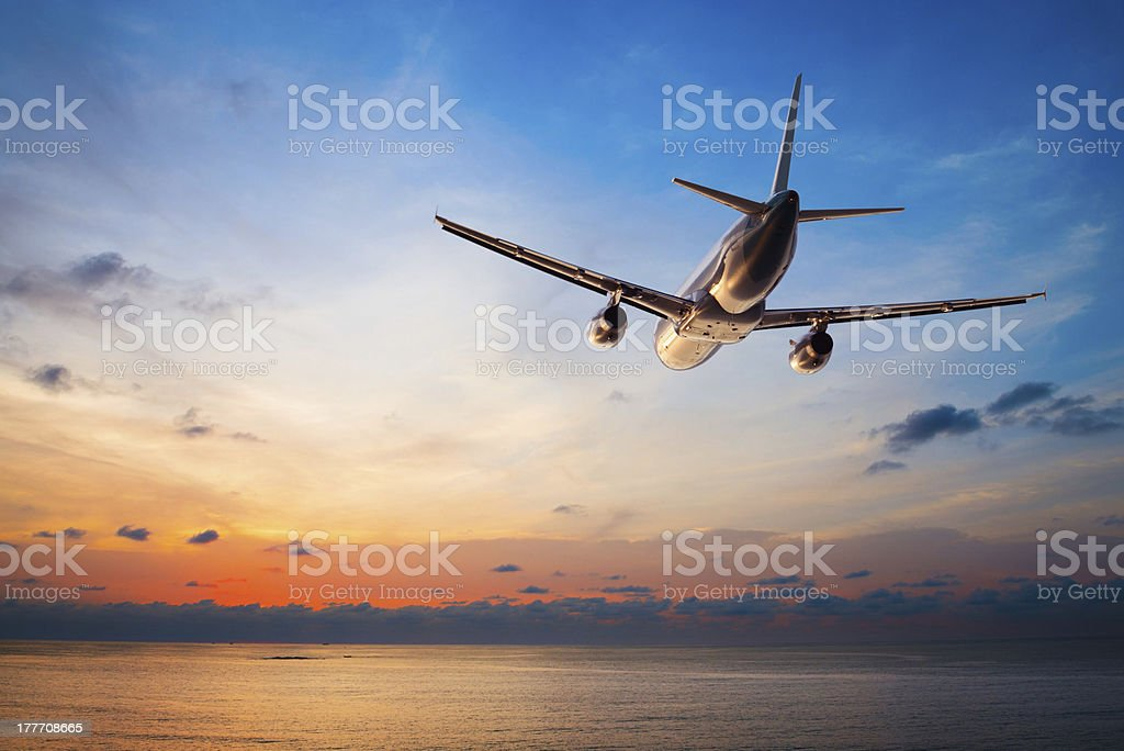 Airplane flying at sunset stock photo