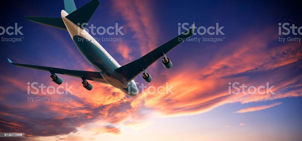 Airplane flying in a cloudy sunset stock photo