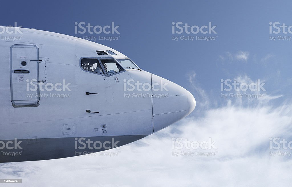 Airplane flying in front of blue sky royalty-free stock photo