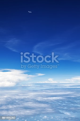istock Airplane flying in mid air above clouds. Clear sky background 661990262