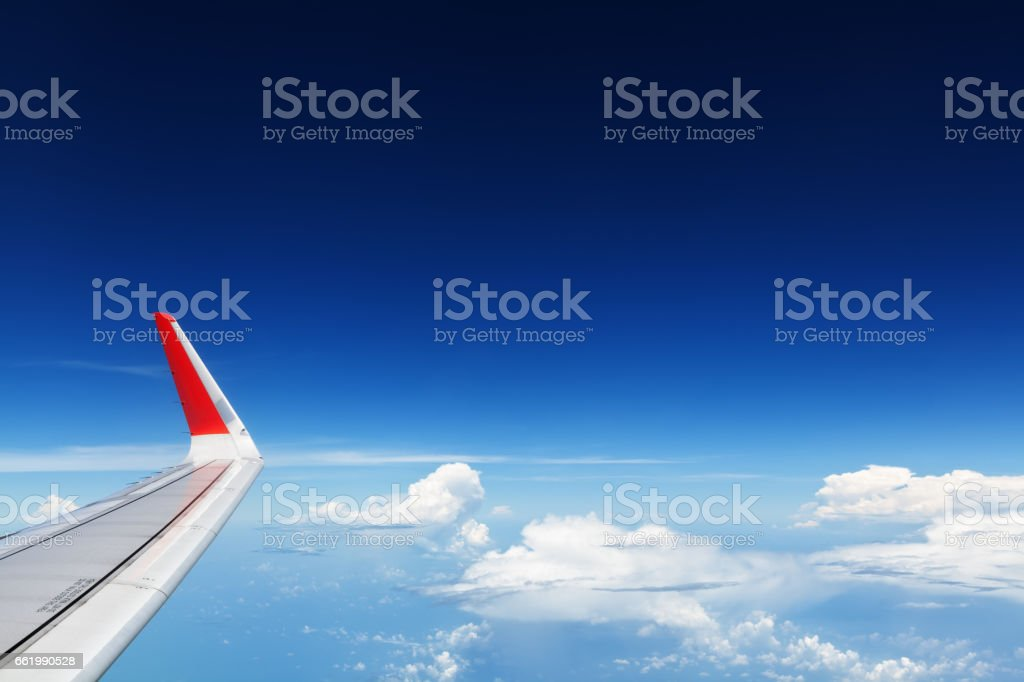 Airplane flying in mid air above clouds. Clear sky background royalty-free stock photo