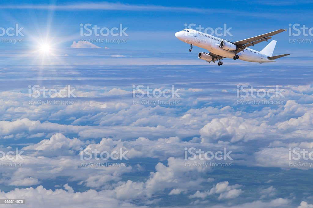 airplane flying in sky high altitude above the white clouds stock photo