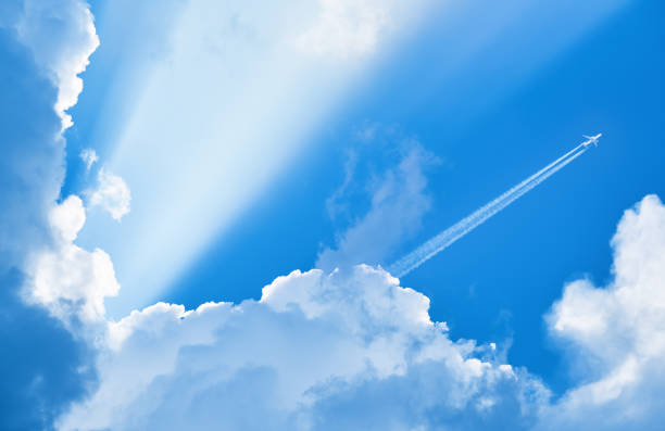 Airplane flying in the blue sky among clouds and sunlight stock photo