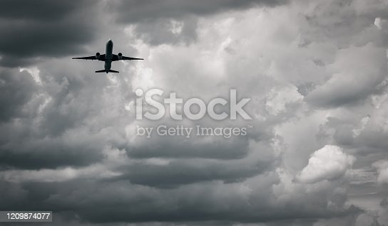 istock Airplane flying on dark sky and white clouds. Commercial airline with dream destinations concept. Aviation business crisis concept. Failed journey vacation flight. Air transportation. Sad travel. 1209874077