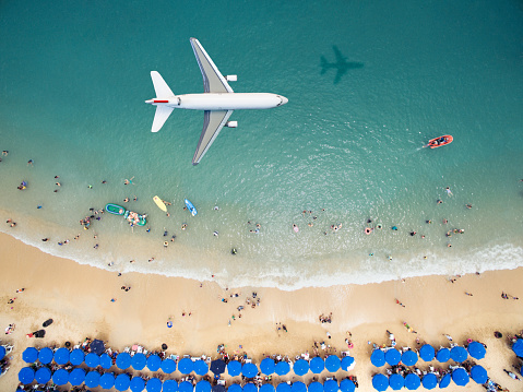 Airplane flying over a crowded beach