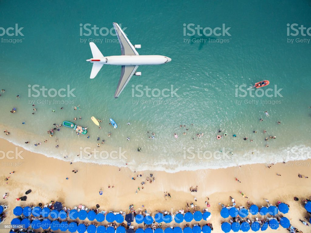 Airplane flying over a crowded beach stock photo