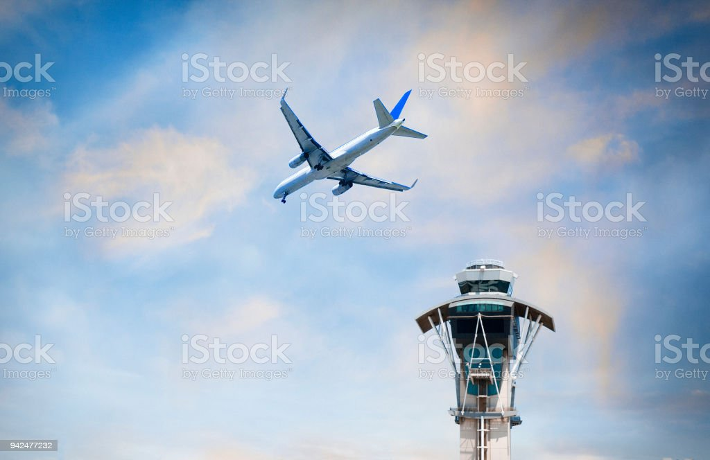 Airplane flying over air traffic control tower stock photo