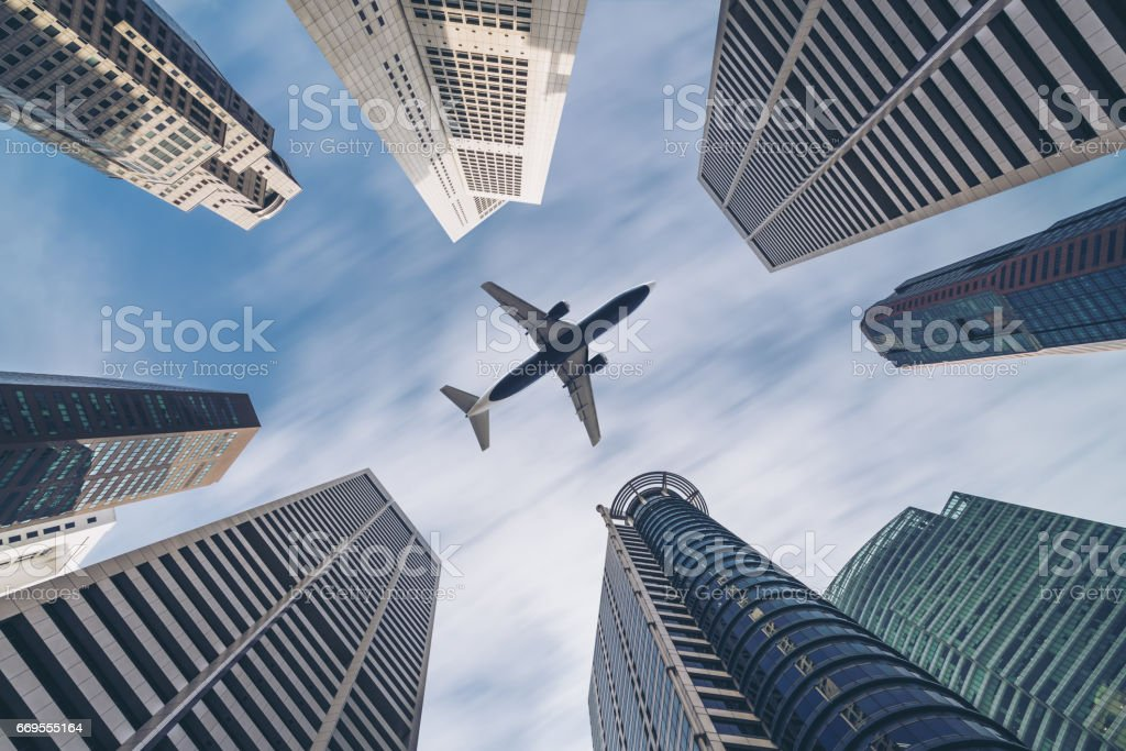 Airplane flying over city business buildings, high-rise skyscrapers stock photo