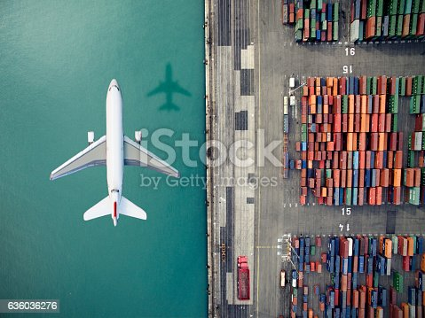 istock Airplane flying over container port 636036276