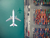 Airplane flying over container port